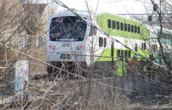 GO Transit train sits on the tracks where it struck an unidentified person, obscured by trees in this photo, near Greenwood Avenue.