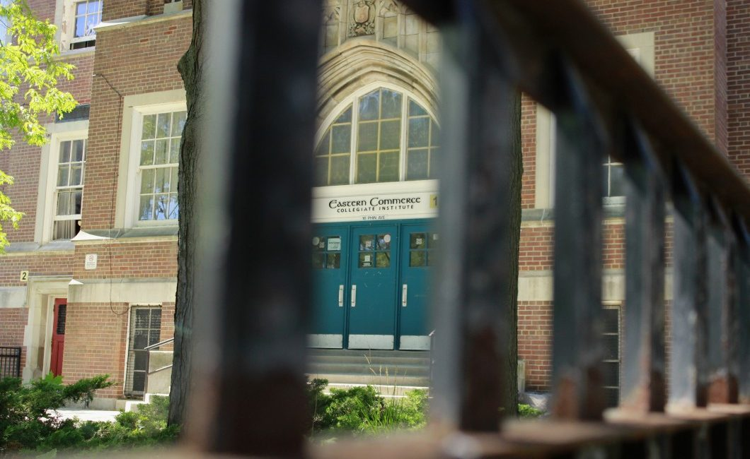 Shows the front doors of Eastern Commerce Collegiate Institute through metal bars.