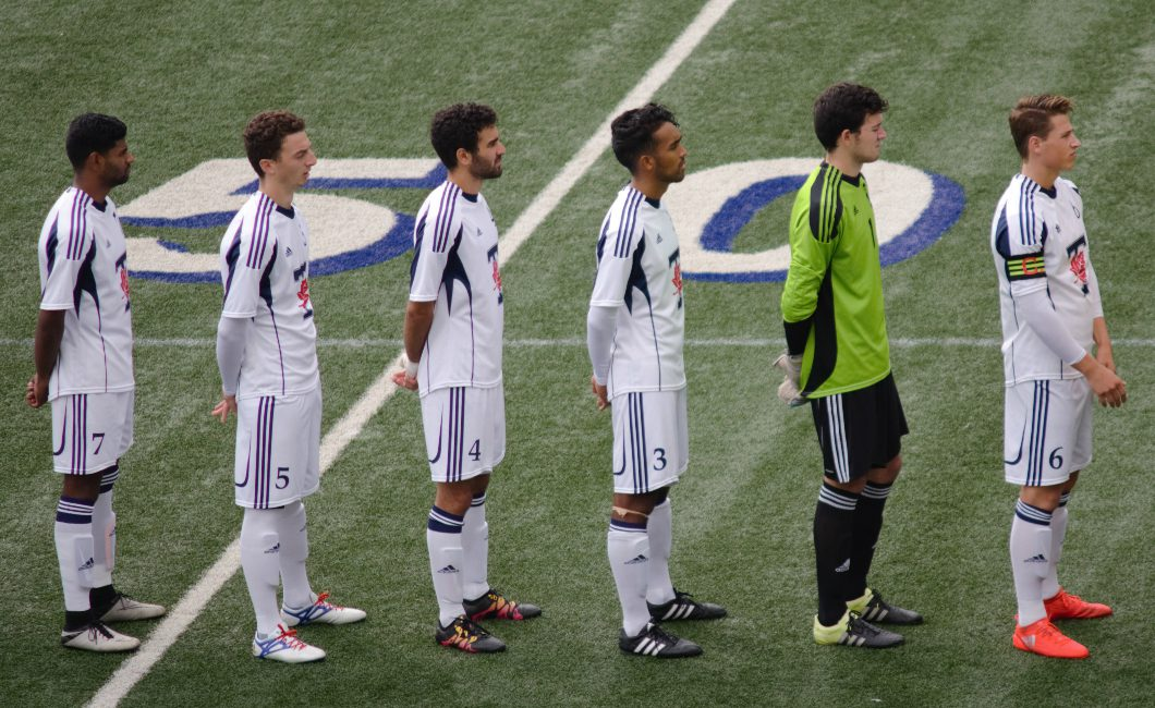 University of Toronto forward Nirun Sivananthan, far-left, and teammates line-up at Varsity Stadium on Sunday before kicking off their second game in less than 24 hours.