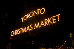 A sign reads 'Toronto Christmas Market' in yellow Christmas lights.