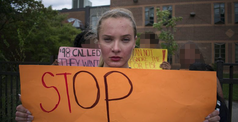 "Quinne Kendall-Mitchell, a grade 10 student at East York Collegiate Institute, stands in front of her school, holding a yellow sign which reads ""Stop excluding LGBTQ."""