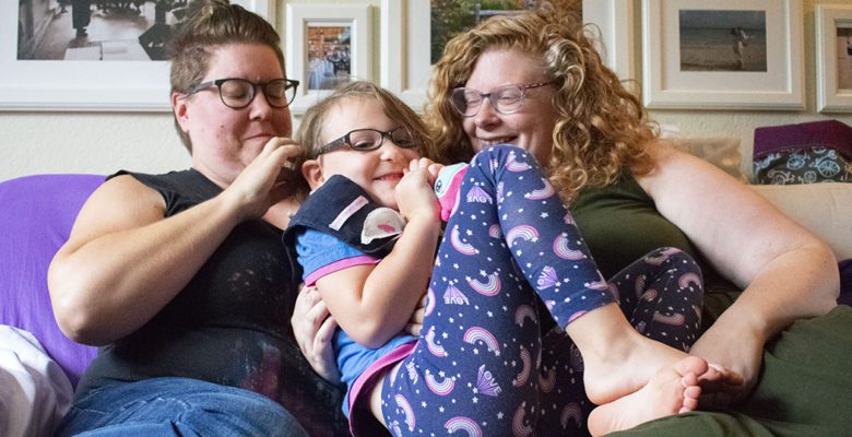Merlin Hargraves (left) and Helen Hargreaves (right) cuddle their child, Eleanore on their couch.