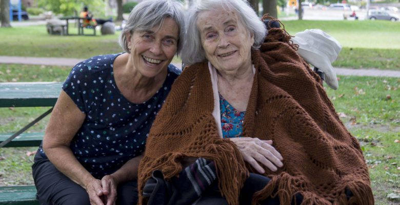 Catherine Staples and Mary Staples (she is in a wheelchair) are smiling for the camera in a park before talking about their lives in East York.