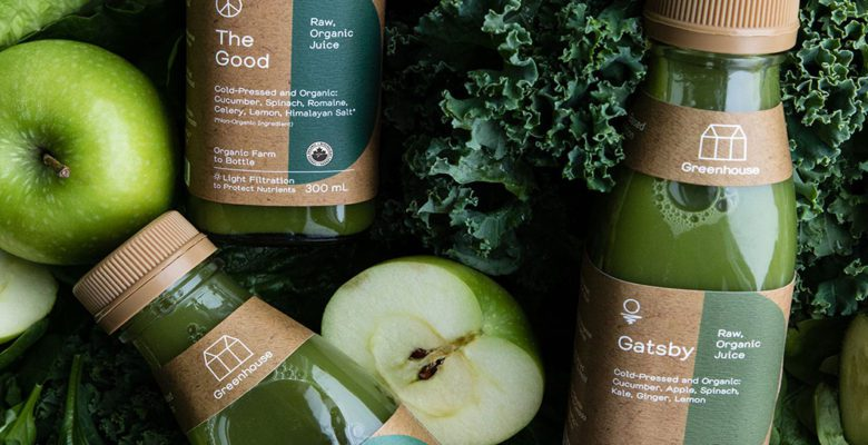 Greenhouse Juice plant-based beverages bottles on a bed of kale, apples, celery and romaine lettuce.