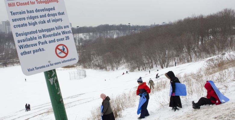 Kids get ready to slide down closed toboggan hill.
