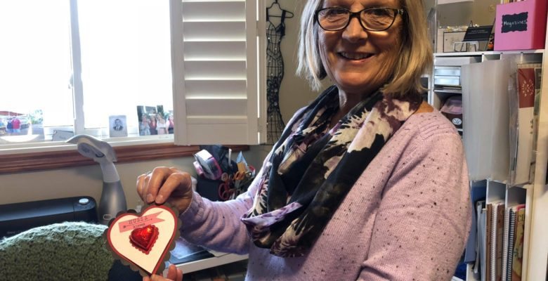 Woman holding a heart-shaped card.