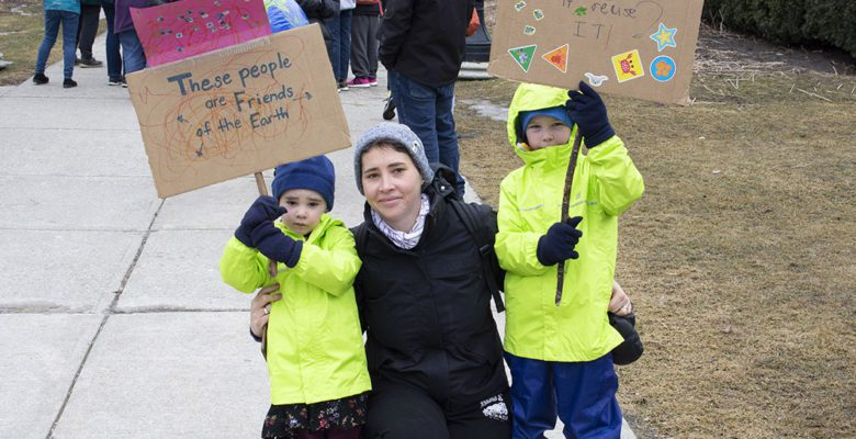 Kids hold up protest signs next to their mother